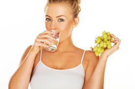 a girl drinking a glass of watet to ensure the health of her skin